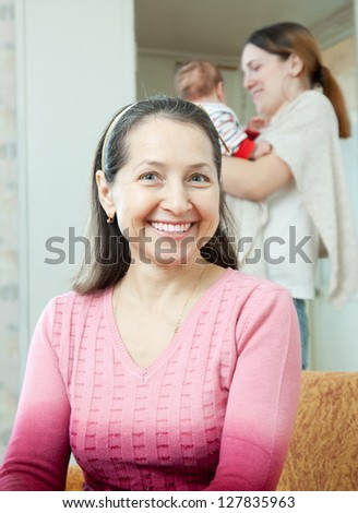 Portrait of happy mature woman against young mother with little baby at home interior. Focus on  grandmother