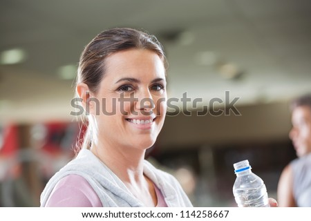Portrait of happy mature woman holding bottle of water at health club