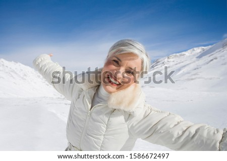Portrait of happy mature woman in mountains on winter day