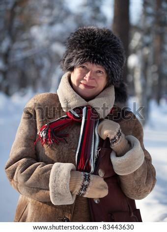 Portrait of happy mature woman in winter park