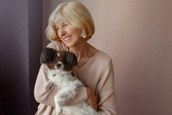 Portrait of happy  mature  woman lovingly hugging pet dog and smiling while enjoying weekend at home. Soft colors.