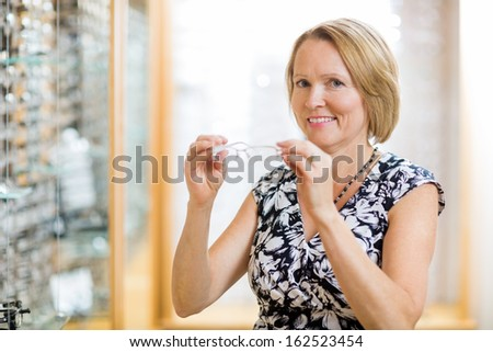 Portrait of happy mature woman trying on glasses at optician store