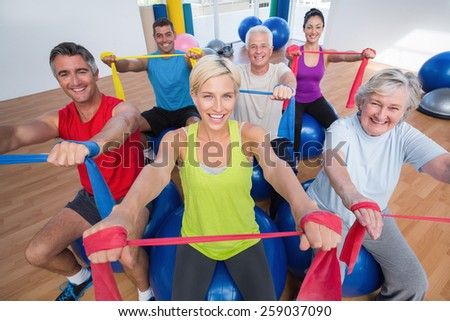 Portrait of happy men and women on fitness balls exercising with resistance bands in gym class #259037090