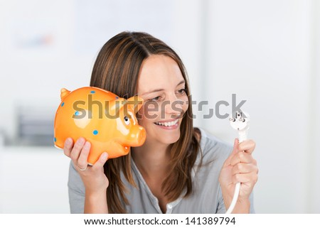 Portrait of happy mid adult businesswoman with electric plug and piggy bank in office
