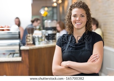 Portrait of happy mid adult female owner standing arms crossed in cafe