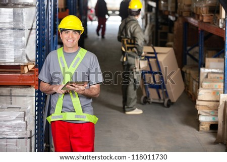 Portrait of happy mid adult foreman with digital tablet and coworker pushing handtruck at warehouse