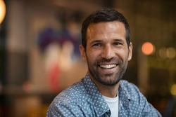 Portrait of happy mid adult man with beard. Close up of successful young entrepreneur in casual smiling and looking away. Hopeful business man smiling sitting in cafe; future and vision concept.
