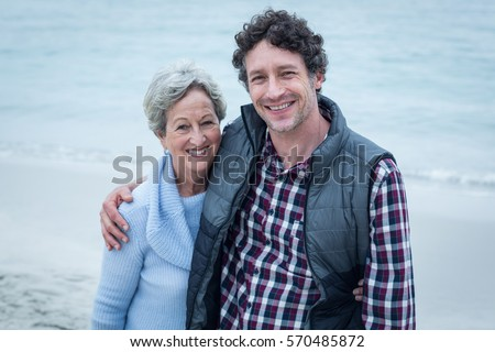 Portrait of happy mid adult man with mother at sea shore