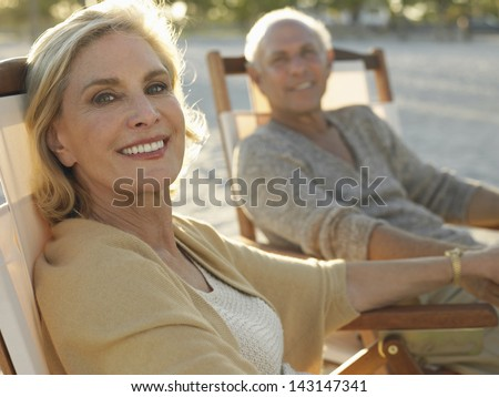 Portrait Of Happy Middle Age Woman With Man Relaxing On Deckchairs At Beach