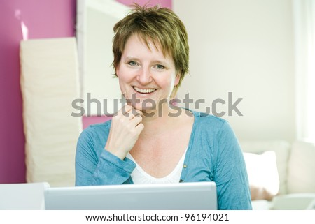 Portrait of happy middle age woman with notebook at home smiling at camera