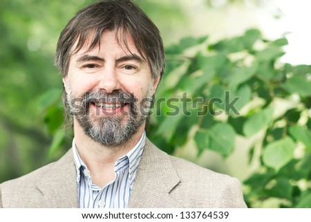 Portrait of happy middle-aged businessman looking at camera and smiling, outdoors #133764539
