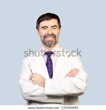 Portrait of happy middle-aged dentist on a pale background, wearing lab coat, dentist mirror in his hand