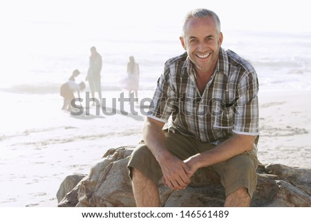 Portrait of happy middle aged man sitting on rock while family enjoying in background at beach