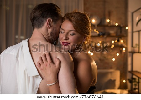Portrait of happy middle-aged woman enjoying hug of her lover in bedroom. She is digging nails into male shoulder skin with passion and smiling. Copy space #776876641