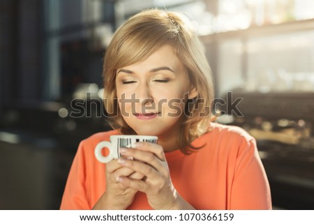 Portrait of happy middle aged woman in cafe enjoying coffee with closed eyes. Enjoyment, lifestyle, rest concept #1070366159