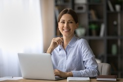Portrait of happy millennial Caucasian businesswoman work on laptop online at home office. smiling young woman employee or worker consult client partner distant on computer. Technology concept.