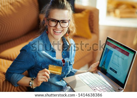 Portrait of happy modern woman with opened on laptop online travel & booking agency site holding gold credit card in the modern living room in sunny summer day. #1414638386