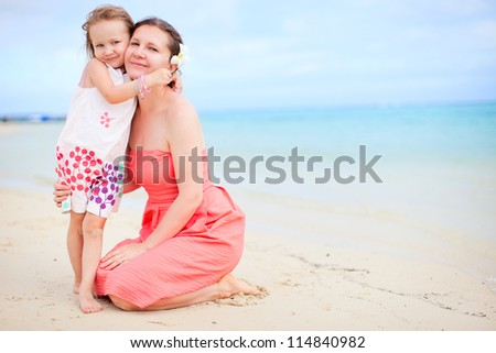 Portrait of happy mother and daughter at beach