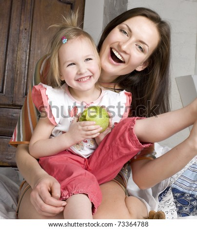 portrait of happy mother and daughter in bed, smiling hugging, holding green apple