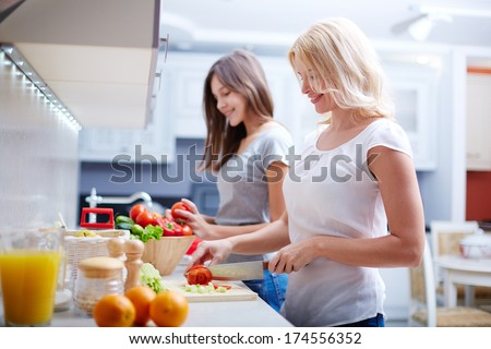 Portrait of happy mother and her daughter cooking in the kitchen
