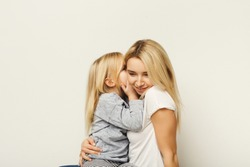 Portrait of happy mother and little daughter at white studio background. Cute kid whispering secret on her mom ear. Trust, secrecy, care and support, mother`s day greeting card mockup, copy space