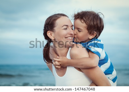 Portrait of happy mother and son at sea, outdoor