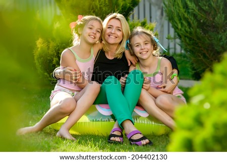 Portrait of happy mother and two daughters sisters twins in the summer garden of his country house. Photo shows a cheerful smile on the faces of people having a rest.
