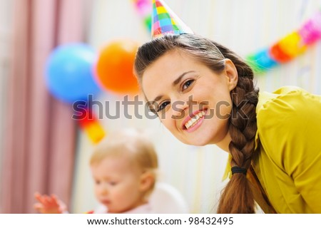 Portrait of happy mother at babies birthday party
