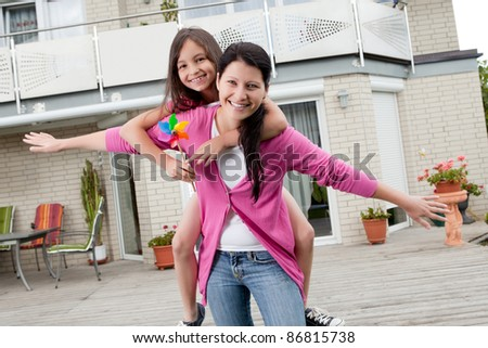 Portrait of happy mother carrying her daughter on back outside their home