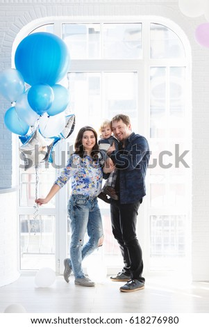 Portrait of happy mother, father and son on his second birthday party indoors. Happy birthday, joyful and laughing two years old baby boy. Young Stylish happy family concept.
