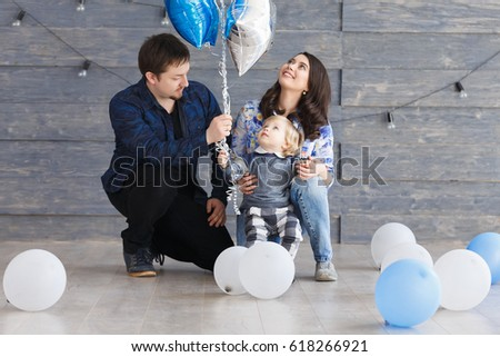 Portrait of happy mother, father and son on his second birthday party with blue and white air balloons, indoors. Happy birthday, joyful and laughing two years old baby boy.