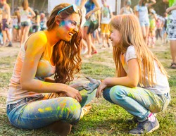 Portrait of happy mother with little daughter on holi color festival