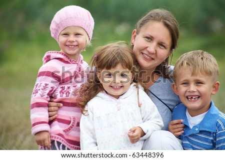Portrait of happy mother with three children outdoors