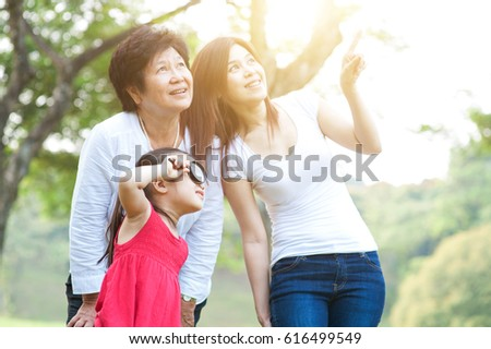 Portrait of happy multi generations Asian family at park. Grandmother, mother and daughter outdoor fun, exploring the nature. Morning sun flare background. #616499549