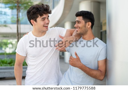 Portrait of happy multiethnic male friends talking and laughing outdoors. Young Indian and Hispanic student standing at college and embracing. Male friendship and relationship concept