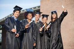 Portrait of happy multiethnic students in graduation gowns holding diplomas on university campus