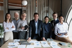 Portrait of happy multiracial businesspeople stand pose at workplace in modern office. Smiling diverse multiethnic employees colleagues show leadership unity. Success, employment concept.