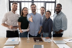 Portrait of happy multiracial businesspeople stretch hand for handshake welcome new colleague or intern in office, smiling diverse multiethnic team meet get acquainted with worker, employment concept