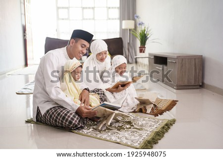 Portrait of happy Muslim family with children reading the Quran and praying together at home.