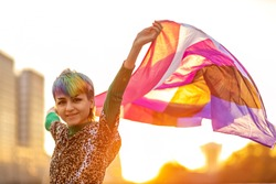 Portrait of happy non-binary person waving gender fluid flag