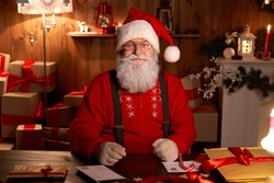 Portrait of happy old bearded Santa Claus wearing hat, glasses, looking at camera, working on Christmas eve sitting at cozy home table late with presents, tree and candles preparing for holidays.