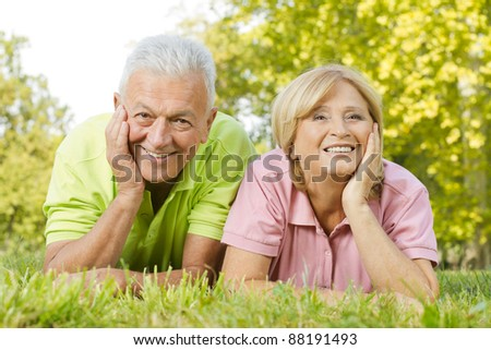 Portrait of happy old people lying on green grass. - stock photo