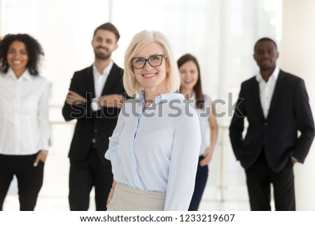Portrait of happy older woman middle aged company ceo, female corporate leader mentor looking in camera with team subordinates, friendly mature executive boss, hr or business coach posing in office