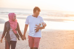 portrait of happy parent with newborn baby at the beach having fun together