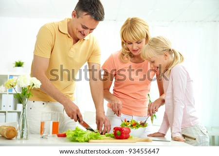 Portrait of happy parents and their daughter cooking salad in the kitchen