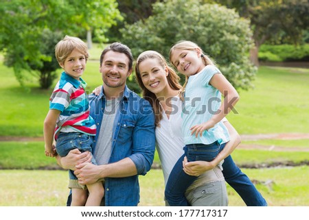 Portrait of happy parents carrying kids at the park #177717317