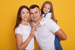 Portrait of happy parents, daddy carries their beautiful daughters on his back. Lovely family of three pose together against yellow background, expressing happuness. Young mother and father with child