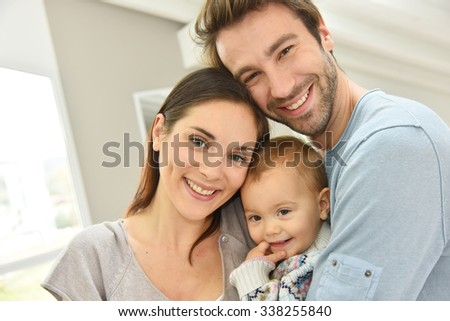 Portrait of happy parents holding baby girl