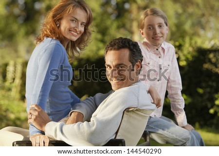 Portrait of happy parents with daughter in backyard