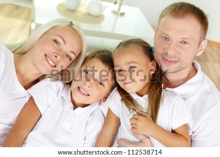 Portrait of happy parents with two children looking at camera at home